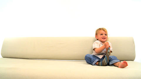 Cute Toddler Sitting On The Sofa And Strips Socks stock footage