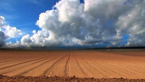 Dramatic Time-lapse Clouds Over A Ploughed Field stock footage