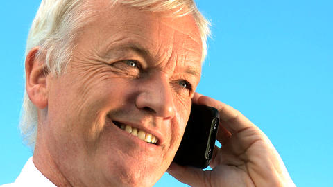 Portrait of mature businessman talking outdoors on a mobile(cell) phone Footage