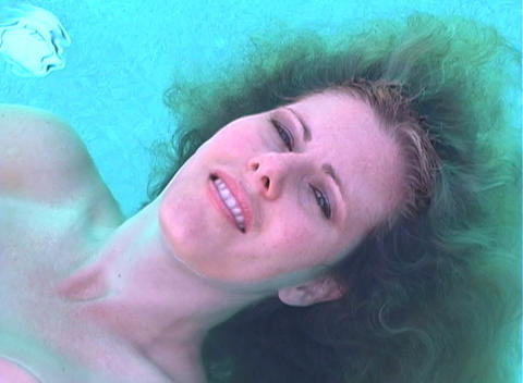 Beautiful Blonde Floating In A Pool-1 stock footage