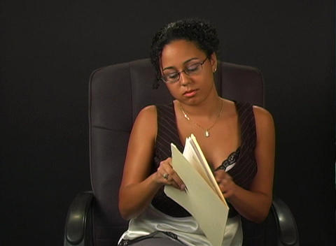 Beautiful Young Woman in an Office Chair with a File Folder Footage