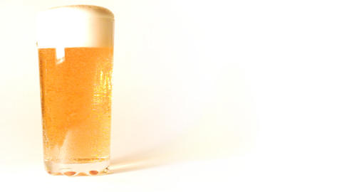 beer is poured into a glass on white background Footage