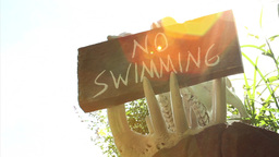 """No Swimming"" Sign In The Jaws Of An Animal Skull stock footage"