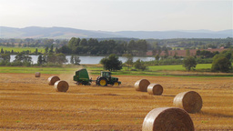 Tractor Passing In A Meadow With Scattered Hay Bal stock footage