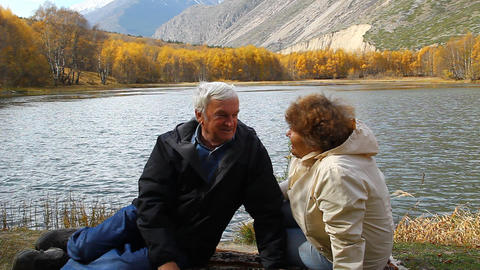 Happy mature man and woman sitting on the shore of Footage