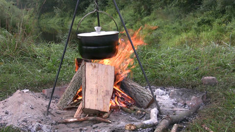 Preparing Food In Pot Above Bonfire 2 stock footage