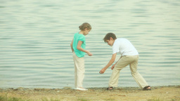 Children Skipping Stones In Lake Footage