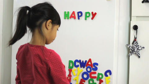 Asian Girl Spelling Happy Birthday On Fridge stock footage