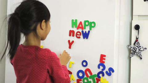 Asian Girl Spelling Happy New Year On Fridge Footage