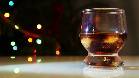 whiskey with ice against festive lights background Footage