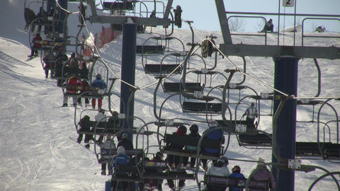Ski lift slowly transports people to the top (High Definition) Footage