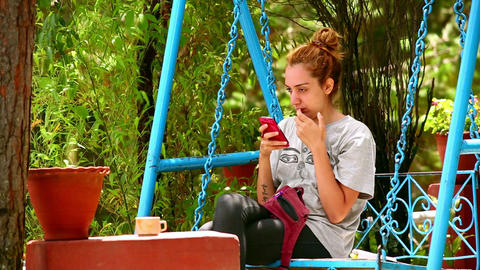 Female Tourist On Swing Using Her Mobile Phone stock footage