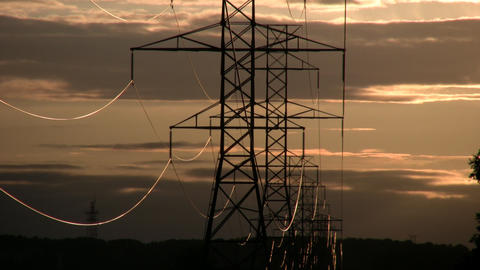 Hydro towers silhouette drifting orange clouds amidst sunset (High Definition) ビデオ