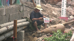Worker reads newspaper in polluted environment in Footage