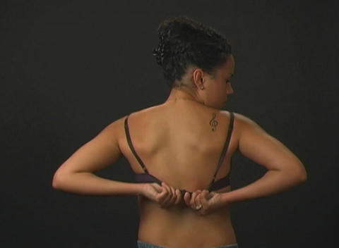 Beautiful Young Woman Putting on Her Bra (1) Footage