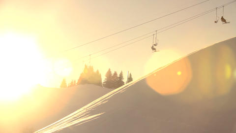 Skiers ride chairlift across frame, silhouetted ag Footage