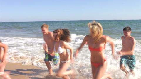 Group Of Teenage Friends Stand In The Sea Before R stock footage