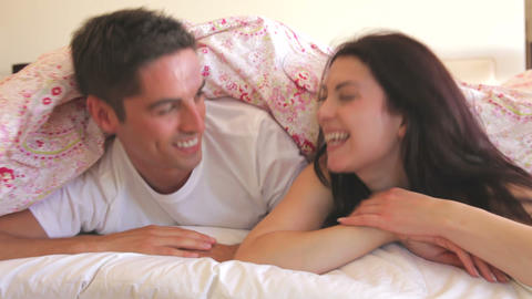 Couple Hiding Under Duvet On Bed Before Pulling It stock footage