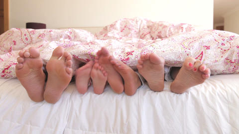 Close Up Of Feet Wriggling As Family Wake Up In Be stock footage