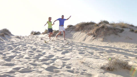 Senior Couple Running Down Sand Dune Together Footage