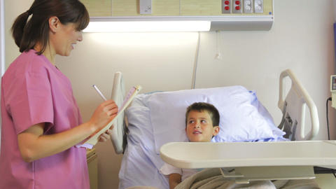 Female Doctor Talking To Boy In Hospital Bed stock footage