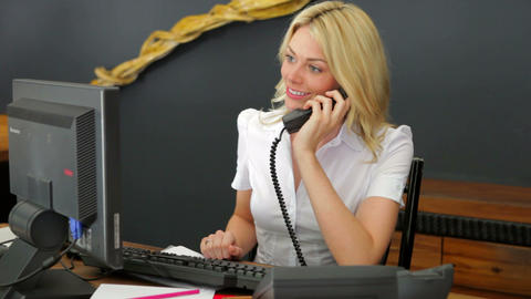 Hotel Receptionist Using Computer And Phone stock footage