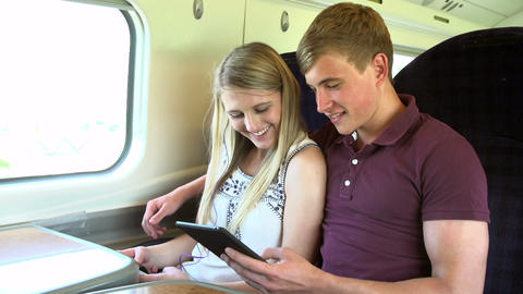 Young Couple Reading E Book On Train Journey Footage