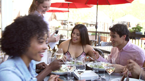 Waitress Pouring Wine For Group Of Friends At Rest stock footage