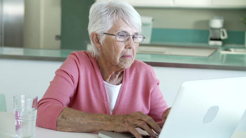 Senior Woman Using Laptop At Home In Kitchen stock footage