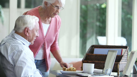 Senior Couple Using Laptop On Desk At Home stock footage