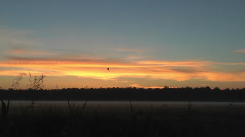 Hot-air Balloon Over Landscape During Sunrise stock footage