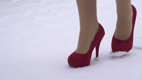 SLOW MOTION: woman in high heels walking in the sn Footage