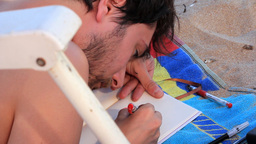 Young man laying on sand,drawing something Footage