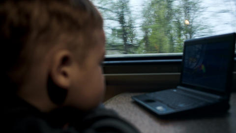 Boy Watching Movie Or Cartoon On Laptop In The Tra stock footage