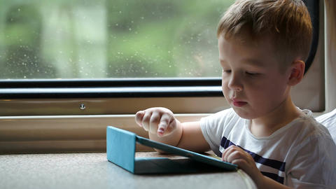 Boy Playing On Pad In The Train Trying To Win With stock footage