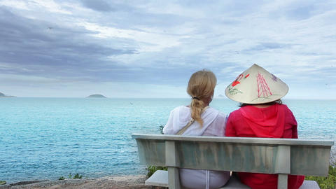 Two Women Sitting On A Bench Talking At The Sea stock footage