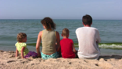 Behind Family Of Four Sitting On Beach stock footage