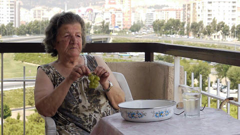 Old retired woman eating grapes on balcony Footage