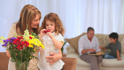 Child Smelling Flowers With Her Grandmother stock footage