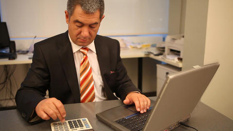 Businessman working on laptop in office, calculating Footage