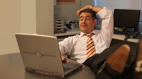 Relaxed businessman working on laptop in office Footage
