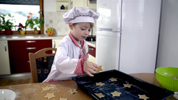 Kitchen and little baker putting cookies on tray Footage