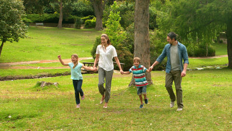 Happy family skipping in the park Footage