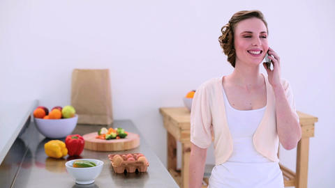 Pretty Model Standing In Kitchen Talking On The Ph stock footage