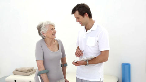 Physiotherapist Talking With Senior Patient On Cru stock footage