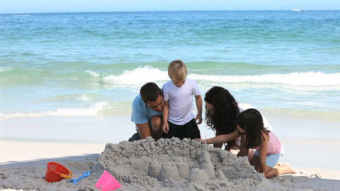 Happy family building a sand castle Footage