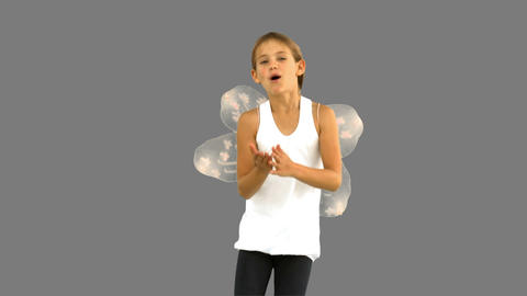 Little Girl Wearing Dragonfly Wings On Grey Screen stock footage