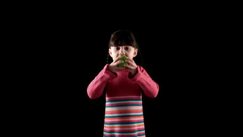 Girl Eating Apple On Black Background stock footage