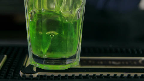 Bartender Pouring A Glass Of Ice With Mint Syrup stock footage