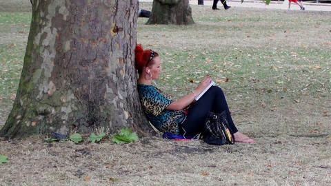Girl leaning under a tree - smokes cigarette and r Footage